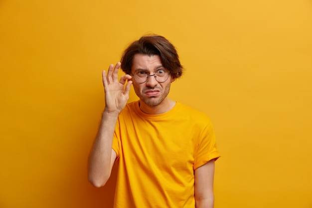 Photo d'un homme adulte mécontent non impressionné façonne un très petit objet, démontre quelque chose de peu, a un regard scrupuleux, porte des lunettes rondes transparentes, isolé sur un mur jaune