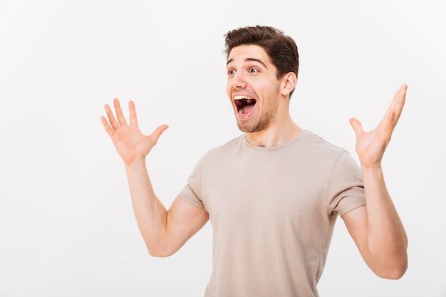 Photo d'un homme adulte non rasé criant et levant les bras de plaisir, isolé sur mur blanc
