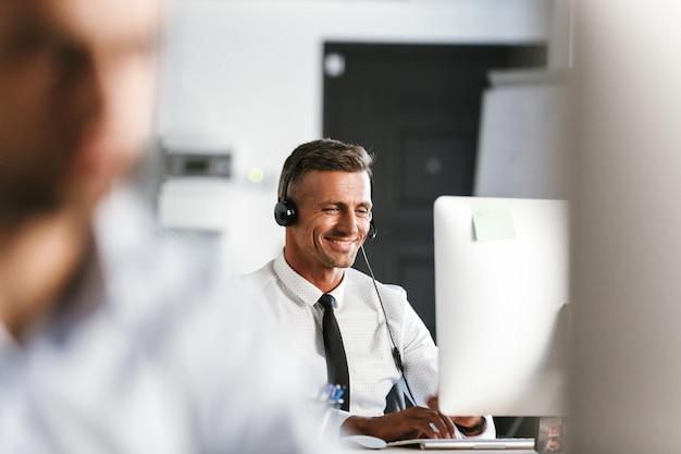 Photo d'un homme d'affaires de 30 ans portant des vêtements de bureau et un casque, souriant alors qu'il était assis par ordinateur dans le centre d'appels