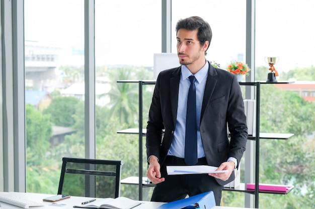Une photo d'un homme d'affaires à un bureau à l'aide de documents