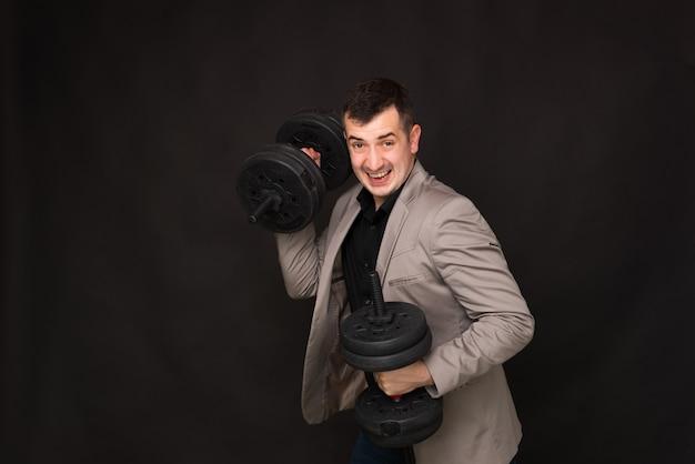 Photo d'homme d'affaires détenant des haltères, concept de puissance métallique d'entreprise, debout sur fond gris