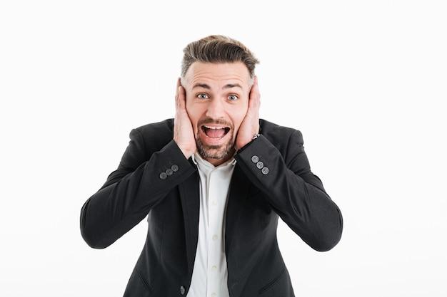 Photo d'un homme d'affaires excité en costume criant à la caméra et couvrant ses oreilles avec les deux mains, isolé sur blanc