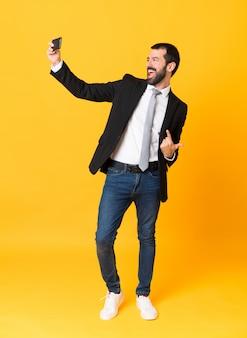 Photo de l'homme d'affaires sur fond jaune isolé faisant un selfie