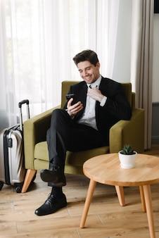 Photo d'un homme d'affaires heureux et apaisant portant un costume noir faisant un appel vidéo sur un téléphone portable alors qu'il était assis sur un fauteuil dans un appartement de l'hôtel