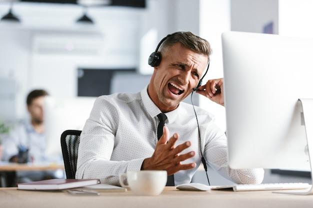 Photo d'un homme d'affaires nerveux de 30 ans portant des vêtements de bureau et un casque, criant alors qu'il était assis devant un ordinateur