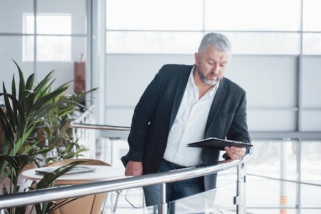 Photo d'homme d'affaires senior dans la salle spacieuse avec des plantes et une table. tenir et lire des documents