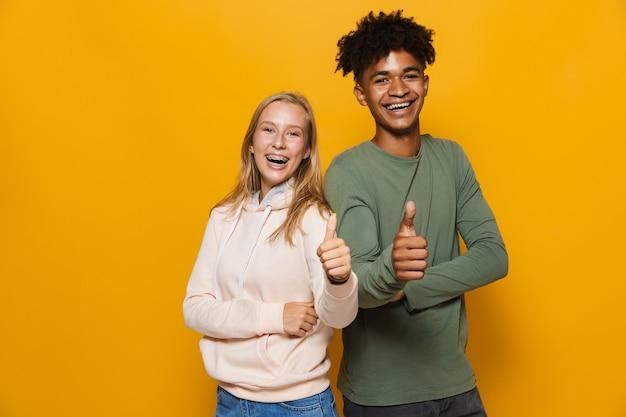 Photo d'un homme afro-américain et d'une femme caucasienne de 16 à 18 ans avec un appareil dentaire faisant des gestes à la caméra, isolé sur fond jaune