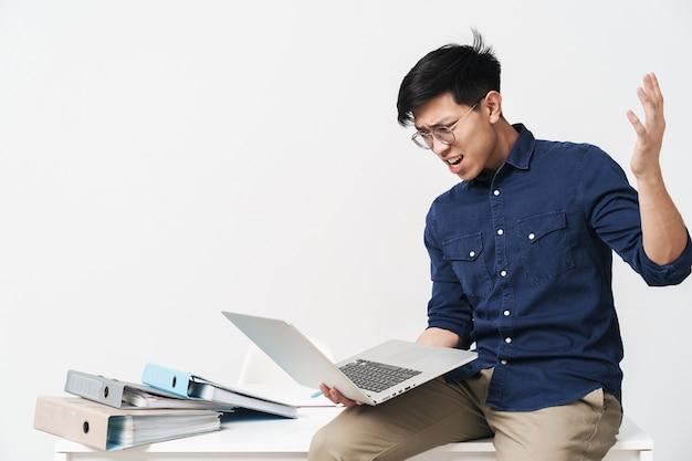 Photo d'un homme asiatique en colère portant des lunettes assis à table et travaillant sur un ordinateur portable au bureau isolé sur un mur blanc