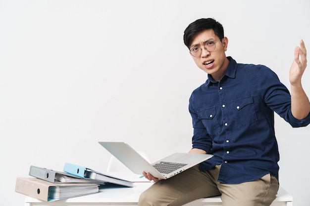 Photo d'un homme asiatique perplexe portant des lunettes assis à table et travaillant sur un ordinateur portable au bureau isolé sur un mur blanc