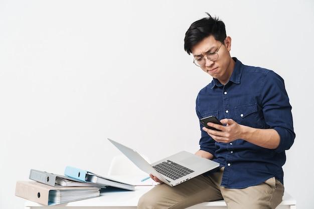 Photo d'un homme asiatique sérieux portant des lunettes tenant un smartphone et un ordinateur portable tout en travaillant au bureau isolé sur un mur blanc