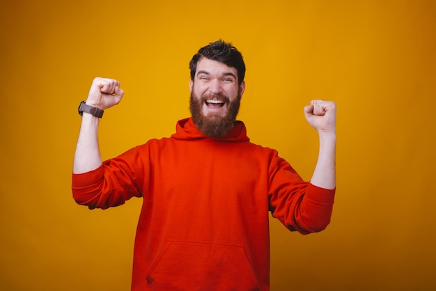 Photo d'un homme barbu excité tient le geste du vainqueur sur l'espace jaune.