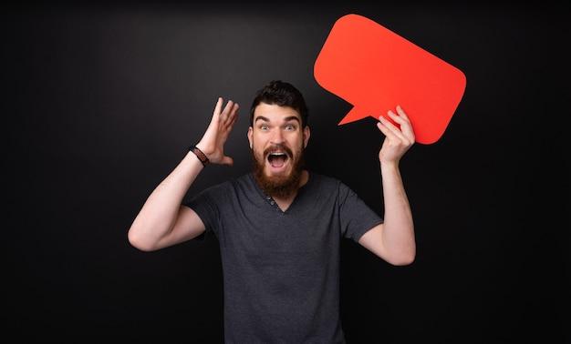 Photo d'un homme barbu frustré tenant un discours de bulle rouge sur fond sombre