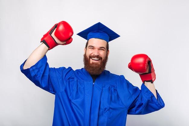 Photo d'un homme barbu gai en baccalauréat diplômé et célébrant avec des gants de boxe rouges