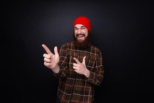 Photo d'un homme barbu montrant quelqu'un et flânant sur un mur sombre