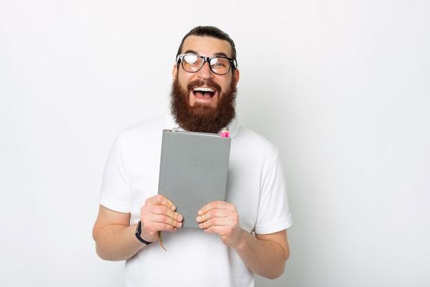 Photo d'un homme barbu souriant et joyeux tenant son agenda ou son planificateur gris