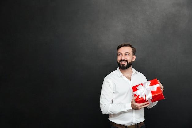 Photo d'un homme barbu souriant tenant une boîte cadeau rouge avec un ruban blanc et regardant de côté sur un mur gris foncé
