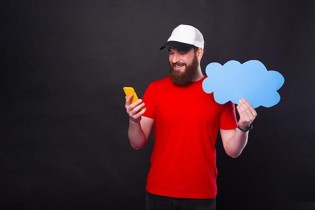 Photo d'un homme barbu en t-shirt rouge à l'aide de smartphone et tenant le discours de nuage bleu