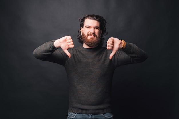Photo d'un homme barbu triste montrant les pouces vers le bas sur dark