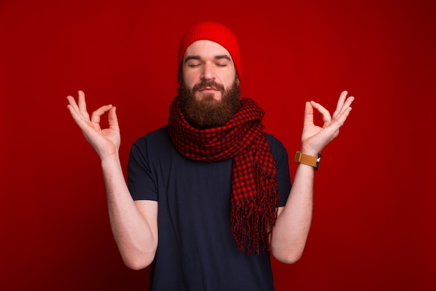 Photo d'un homme barbu, les yeux fermés, faisant un geste zen, sur un espace rouge