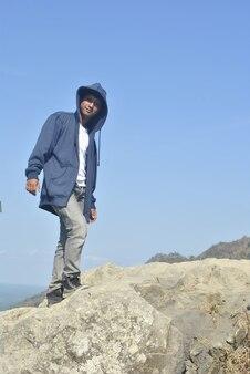 Photo d'un homme sur une belle falaise avec vue derrière lui premium