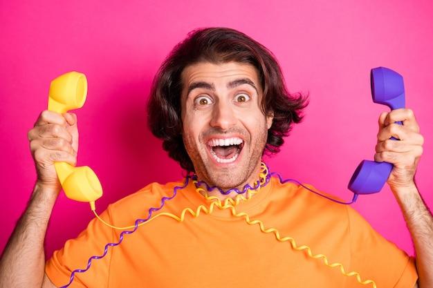 Photo de l'homme bouche ouverte rire tenir deux câbles de téléphone porter un t-shirt orange isolé sur fond de couleur rose
