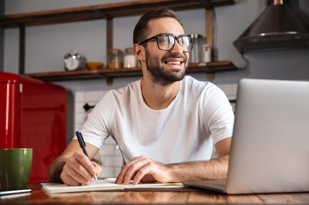 Photo d'un homme brune de 30 ans portant des lunettes d'écrire des notes tout en utilisant un ordinateur portable argenté sur la table de cuisine