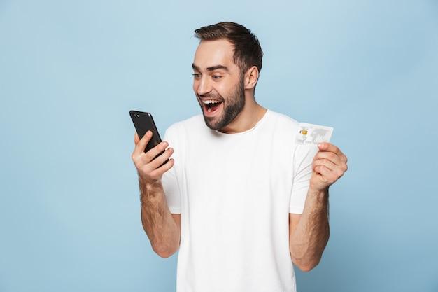 Photo d'un homme caucasien excité en t-shirt blanc décontracté se réjouissant tout en tenant une carte de crédit et un smartphone isolés sur un mur bleu