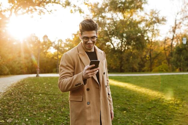 Photo d'un homme caucasien heureux portant un manteau écoutant de la musique avec des écouteurs et utilisant un smartphone en marchant dans un parc d'automne