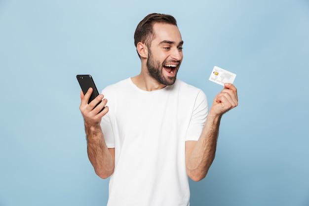 Photo d'un homme caucasien séduisant en t-shirt blanc décontracté se réjouissant tout en tenant une carte de crédit et un smartphone isolés sur un mur bleu