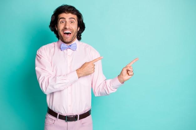 Photo d'un homme doux choqué surpris habillé en tenue rose pointant deux doigts sur l'espace vide isolé sur fond de couleur turquoise