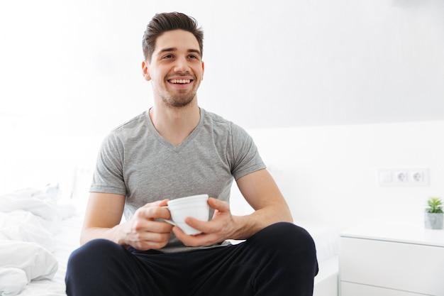 Photo de l'homme du matin heureux en t-shirt souriant assis dans la chambre et buvant du thé ou du café