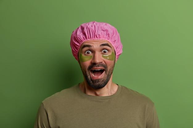 Photo d'un homme effrayé et émotionnel regarde avec les yeux sortis et hurle de peur, applique des tampons de collagène sous les yeux, reçoit des soins de beauté, porte un chapeau de bain protecteur, se tient à l'intérieur. bien-être, beauté