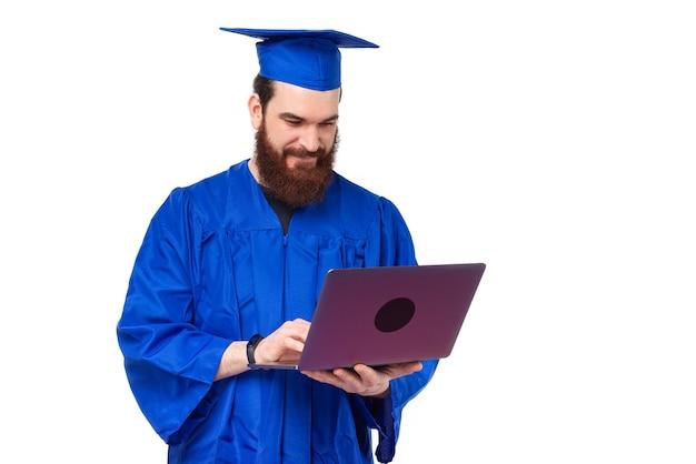 Photo de l'homme étudiant en baccalauréat bleu à l'aide d'un ordinateur portable sur fond blanc