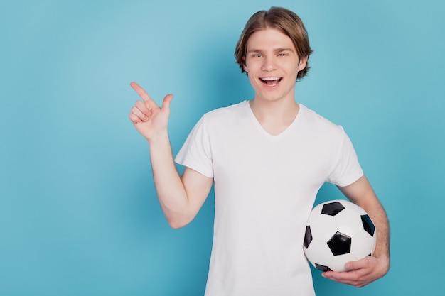 Photo d'un homme excité positif tenant un ballon de football pointer du doigt l'espace vide isolé sur fond bleu