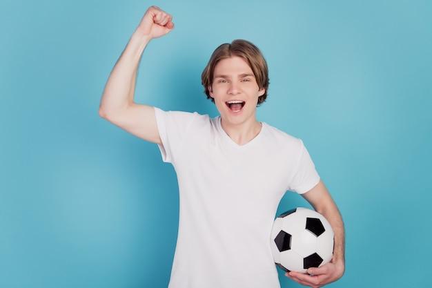 Photo d'un homme extatique positif tenant un ballon de football sur fond bleu isolé