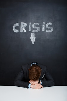 Photo d'un homme fatigué sur tableau noir avec inscription de crise