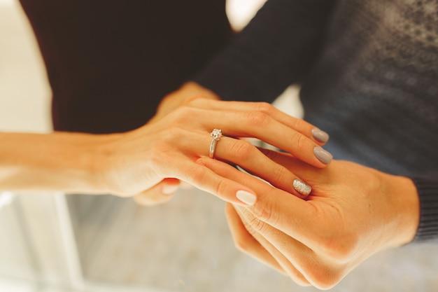 Photo d'un homme et d'une femme avec une alliance, les jeunes mariés choisissent et achètent une alliance dans une bijouterie.