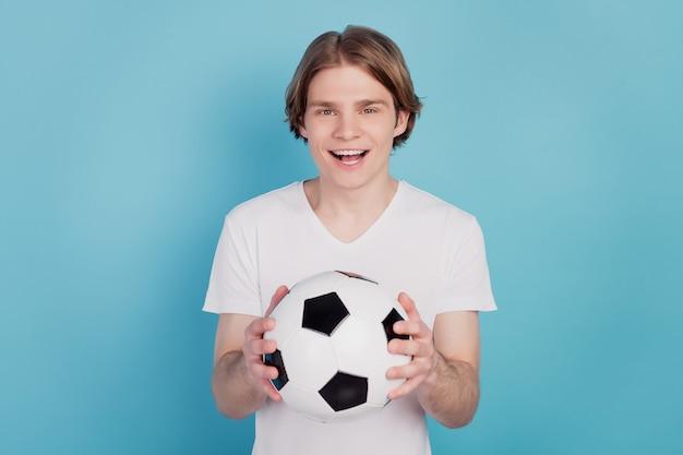 Photo d'un homme fou positif tenant un ballon de football sur fond bleu isolé