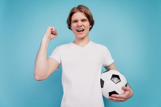 Photo d'un homme fou positif tenant un ballon de football lever le poing sur fond bleu isolé