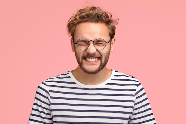 Photo d'un homme gai attrayant rit positivement à la caméra, garde les yeux fermés