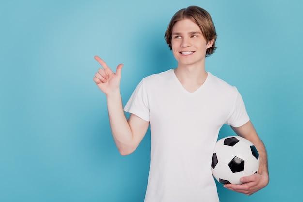 Photo d'un homme gai pointer du doigt l'espace vide tenant un ballon de football fond bleu isolé