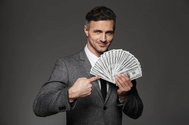 Photo d'un homme heureux de 30 ans en costume officiel démontrant beaucoup de billets en dollars d'argent et pointant le doigt sur les factures, isolé sur mur gris