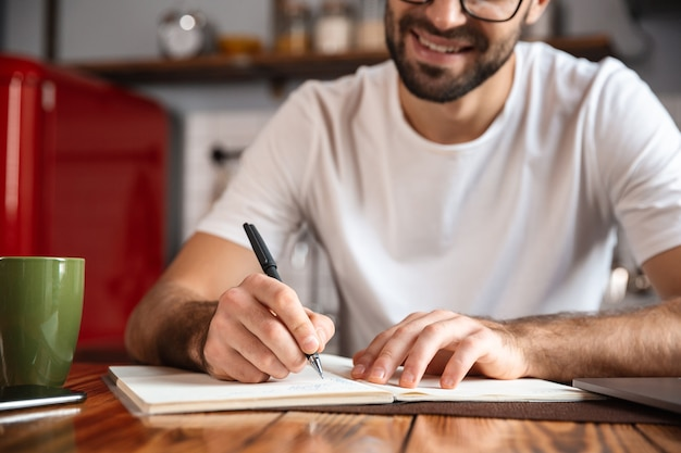 Photo d'un homme heureux de 30 ans portant des lunettes d'écrire des notes tout en utilisant un ordinateur portable argenté sur la table de cuisine