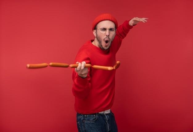Photo d'un homme heureux avec une barbe dans des verres et des vêtements rouges. joue des saucisses comme des nunchucks ninja, isolé sur fond rouge.