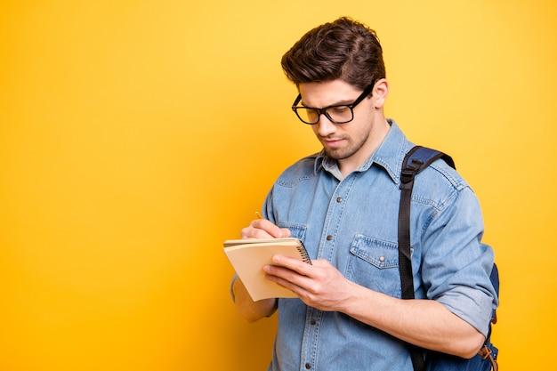 Photo de l'homme intéressé concentré la planification de l'organisation de son avenir avec sacoche derrière son dos isolé l'écriture de nouveaux vers sur un mur de couleurs vives