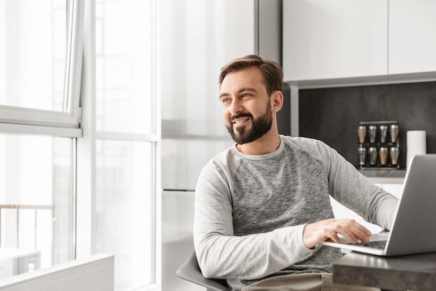 Photo d'un homme joyeux des années 30 en chemise décontractée travaillant sur un ordinateur portable à la maison et regardant par la fenêtre