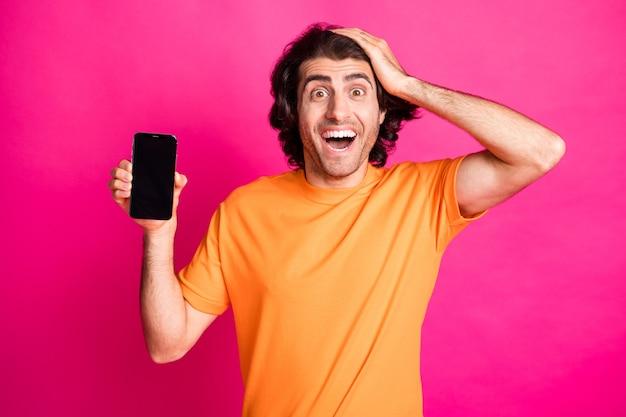 Photo de l'homme main tête tenir téléphone espace vide bouche ouverte porter un t-shirt orange isolé sur fond de couleur rose