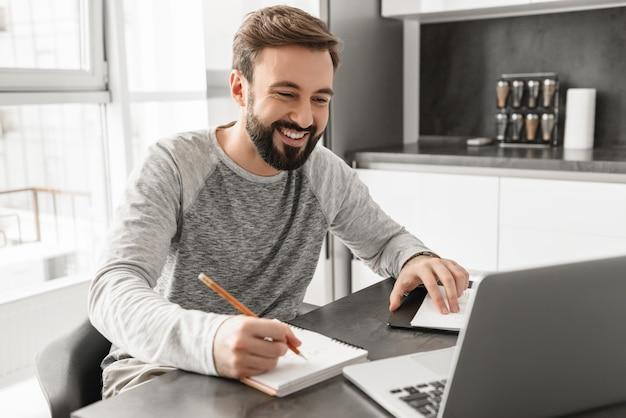 Photo d'un homme mature de 30 ans dans des vêtements décontractés en souriant et en écrivant des notes sur papier et à l'aide d'un ordinateur portable, tout en travaillant dans la chambre avec fenêtre