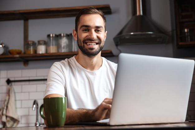 Photo d'un homme mature de 30 ans portant un t-shirt décontracté à l'aide d'un ordinateur portable argenté alors qu'il était assis à table dans un appartement moderne