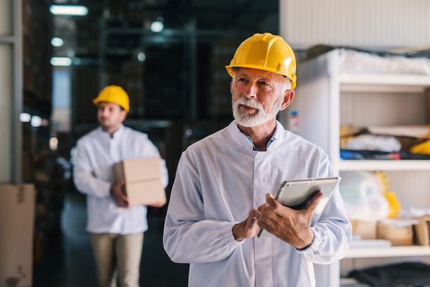 Photo d'un homme mature avec casque sur la tête est debout dans l'entrepôt avec tablette dans ses mains. regarder ailleurs.
